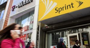 A  woman using a cell phone walks past T-Mobile and Sprint stores in New York. (AP Photo/Mark Lennihan, File)