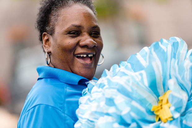 Giant paper flowers brings a smile from Anita Crockett, office manager with Bon Secours Community Works. (Photo by Amy Deputy)