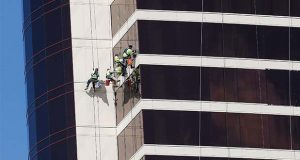 FILE - In this May 22, 2019, file photo window washers work on Encore Boston Harbor in Everett, Mass. On Thursday, June 6, the Labor Department issues revised data on productivity in the first quarter. (AP Photo/Michael Dwyer, File)