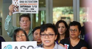 Demonstrators hold placards as Rey Wences, organizer at Organized Communities Against Deportations (OCAD) addresses reporters during a new conference outside the U.S. Citizenship and Immigration Services offices in Chicago, Thursday, July 11, 2019. A nationwide immigration enforcement operation targeting people who are in the United States illegally is expected to begin this weekend. (AP Photo/Amr Alfiky)