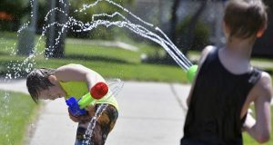 Jaxon Claymore, 8, left, and his older brother Jalen, 9, battle each other with large water guns in the hot midday sun in front of their apartment building on Wednesday, July 17, 2019, Bismarck, N.D. The pair say they compete against one another at home and in school to see who is the best in sports from running, throwing and strength. The weather forecast for the area calls for temperatures in the 80s with little chance of rain for the next several days. (Mike McCleary/The Bismarck Tribune via AP)