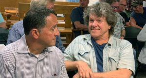 FILE - In this Tuesday, July 16, 2019, file photo, Michael Lang, right, Woodstock 50 co-producer and co-founder, sits in Vernon Town Hall before a planning board hearing in Vernon, N.Y., for his appeal to grant a permit for the Woodstock 50 music festival. Woodstock 50 organizers have again been denied a permit to hold a three-day festival at an upstate New York horse track. Town of Vernon officials say Monday, July 22, 2019, the permit application for a festival Aug. 16-18 at the Vernon Downs racetrack and casino was filed too late and was rife with problems. (Edward Harris/Observer-Dispatch via AP)