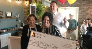 """Howard Bank Mary Ann Scully, left, presents a ceremonail $10,000 checck to Rise 'N Grind owner Angelina Vanderhoef Monday at the coffee shop in Rising Sun for winning Howard Bank's inaugural """"Keep It Local"""" contest. (Submitted photo)"""
