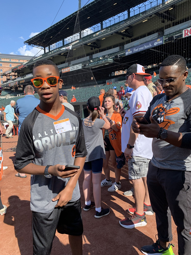 """Nasir Lay spends time on the field at Camden Yards with Baltimore Orioles' players during SECU's """"K's for Kids"""" program. (Photo by Lina Bernstein)"""