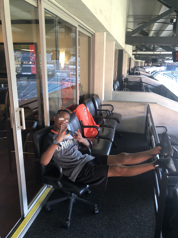 Nasir Lay chills in the SECU corporate box seats while waiting to watch the Orioles play. (Photo by Lina Bernstein)
