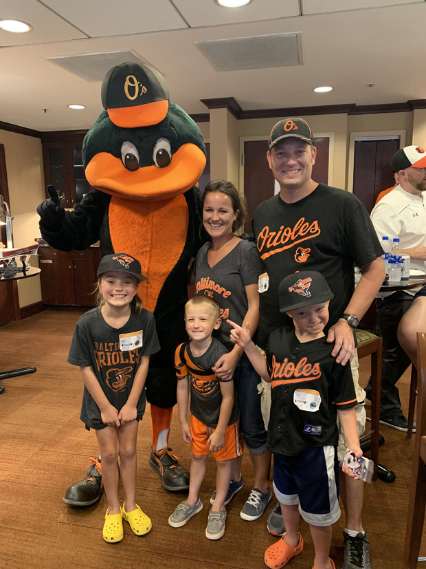 """Elijah Yanike, center, and his family are all smiles with the Oriole Bird when they visited Camden Yards through SECU's """"K's for Kids"""" program. (Photo by Lina Bernstein)"""