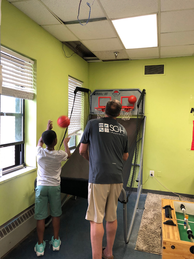 Barry Offutt, director, spends some time shooting hoops with a youth while volunteering at the Boys and Girls Club. (Photo courtesy of SC&H Group)