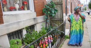 Lorraine Diggs stands on the sidewalk outside her rowhouse in East Baltimore on July 9, 2019. Diggs is passionate about maintaining the trees outside of her home and has dedicated a small garden in front of her house to her late mother. (University of Maryland Photo/Maris Medina)