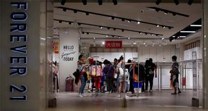 FILE - In this Tuesday, May 7, 2019, file photo, women select clothing at an American fast fashion retailer Forever 21 which is offering clearance discounts at a shopping mall after it pulled out from China's market, in Beijing. Low-price fashion chain Forever 21, a one-time hot destination for teen shoppers that fell victim of its own rapid expansion and changing consumer tastes, announced Sunday, Sept. 29, 2019, that it has filed for Chapter 11 bankruptcy protection. (AP Photo/Andy Wong, File)