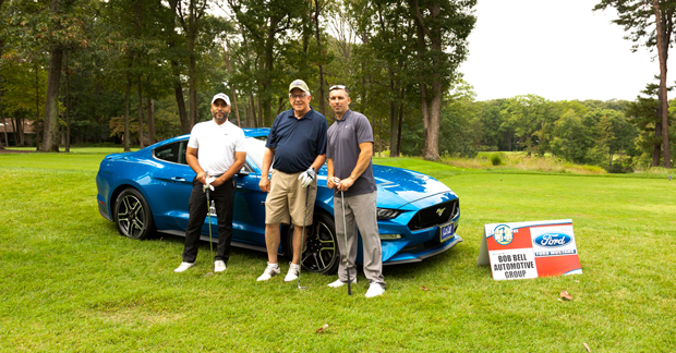 From left, Myron Patteron, pre-owned sales manager with Bob Bell Ford in Glen Burnie; David Coyne, general manager of Bob Bell Ford in Glen Burnie; and James Patton, a Ford sales specialist with Bob Bell Ford in Bel Air; stand in front of a Ford Mustang at the car dealer's second annual charity golf tournament. (Photo by Kevin Scrimgeour)