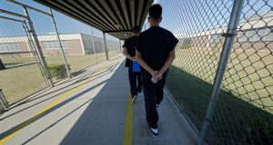 Detainees walk with their hands clasped behind their backs along a line painted on a walkway inside the Winn Correctional Center in Winnfield, La., Thursday, Sept. 26, 2019. Detainees are required to walk from site to site with their hands clasped behind their backs. Since 2018, eight Louisiana jails have started detaining asylum seekers, making Louisiana an unlikely epicenter for immigrant detention under President Donald Trump. Immigration and Customs Enforcement says it's now detaining about 8,000 migrants in Louisiana out of 51,000 nationally. (AP Photo/Gerald Herbert)