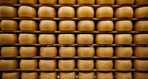 FILE - In this Oct. 8, 2019, file Parmigiano Reggiano Parmesan cheese wheels are stored in Noceto, near Parma, Italy. The tariffs the Trump administration is about to impose on wine, liquor and cheese from Europe couldn't come at a worse time for small retailers. (AP Photo/Antonio Calanni, File)