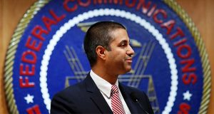 FILE - In this Dec. 14, 2017, file photo, after a meeting voting to end net neutrality, Federal Communications Commission (FCC) Chairman Ajit Pai smiles while listening to a question from a reporter in Washington.  A federal court is ruling that the FCC had the right to dump net-neutrality rules, but couldn't bar states like California from passing their own. The ruling is largely a victory for Pai. (AP Photo/Jacquelyn Martin, File)