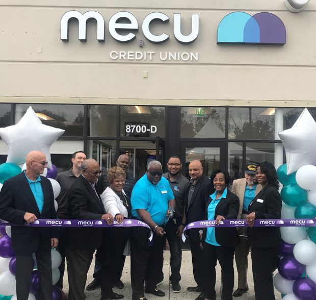 Philip Allen, center, the MECU Randallstown branch manager and director of membership services, cuts the ceremonial ribbon officially opening the credit union's newest branch facility. Joining Allen in the ribbon-cutting ceremony were, from left, Ernest J. Glinka, MECU board member; Tom Poe, a former MECU vice president of marketing; Herman Williams Jr., chairman of the MECU board; Mary Clay, senior outreach coordinator from the office of Baltimore County Executive John Olszewski Jr.; Adrian Johnson, chief financial officer and senior vice president; MECU Credit Union President and CEO John Hamilton, Kathy Shelton, MECU's chief operating officer, and Nina Spencer, MECU's vice president of retail delivery. (Photo courtesy of MECU Credit Union)