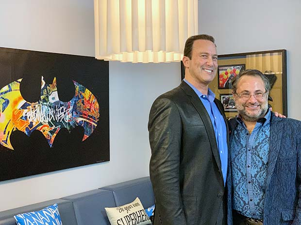Scott Robinson, left, brother of the late Lenny Robinson, and Richard Kurland, CEO of Employment Background Investigations Inc., stand in the new LBR Batman4Ever Lounge at the company's headquarters in Owings Mills. The Lounge was created in memory of Lenny Robinson, who was known for dressing like Batman and visited children in hospitals. (Submitted photo)