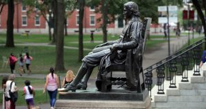 FILE - In this Aug. 13, 2019, file photo, the statue of John Harvard looks over Harvard Yard at Harvard University in Cambridge, Mass. A settlement was announced Wednesday, Nov. 27, in a 2015 federal suit by the National Association of the Deaf, arguing that Harvard failed to provide captioning for its online courses, podcasts and other educational programs. (AP Photo/Charles Krupa, FIle)
