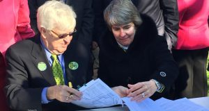 John E. Kyle, president of the State Center Neighborhood Alliance, and Caroline Moore, CEO of Ekistics LLC, managing member of State Center LLC, sign a community benefits agreement for the redevelopment of  State Center in 2016. Kyle said Tuesday that his neighborhood organization has concerns about Gov. Larry Hogan's plans for State Center.  (The Daily Record/File Photo)