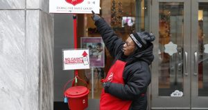 Bbell ringer Carolyn Harper points to two ways to donate via mobile device to the Salvation Army's annual holiday red kettle campaign on Chicago's Magnificent Mile. (AP Photo/Charles Rex Arbogast)