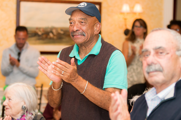 Tony Hawkins, event co-chair and a founding member of HeBros, applauds one of the speakers during the fundraising golf tournament. (Photo courtesy of SEED School)