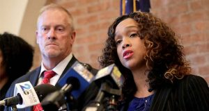 "FILE- In this Dec. 3, 2019 file photo. Maryland corrections secretary Robert Green, left, listens as Maryland State Attorney Marilyn Mosby, right, speaks during a news conference announcing the indictment of correctional officers, in Baltimore. A prosecutor says an investigation that led to the indictment of 25 correctional officers in Baltimore started in 2018 with ""rumors and anecdotes"" about excessive force against jail inmates. Some of those indicted officers faced excessive force claims before the investigation began. (AP Photo/Julio Cortez, File)"