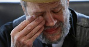 In this Saturday, Dec. 21, 2019 photo, Bobby Goldberg wipes his face at the office of his lawyer, Melissa Anderson, in Bannockburn, Ill. Goldberg has filed a lawsuit claiming he was abused more than 1,000 times in multiple states and countries by the late Donald McGuire, a prominent American Jesuit priest who had close ties to Mother Teresa. (AP Photo/Nam Y. Huh)