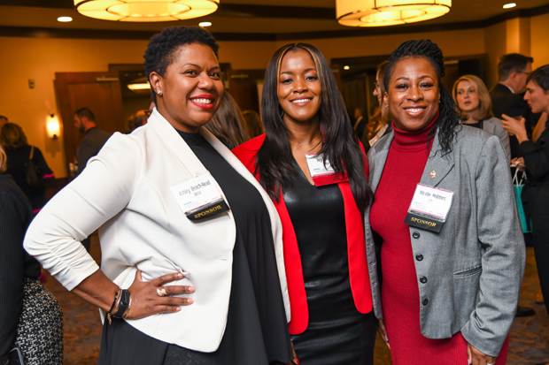 2019 Leading Women winner Ivy Gales, senior business development officer with SECU, center, stands with Ashley Beach-Read, left, and Nicole Holmes. SECU was a Table Sponsor for the event. (Photo by Maximilian Franz)