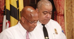 """Baltimore Mayor Bernard C. """"Jack"""" Young and Police Commissioner Michael Harrison observe a moment of silence on Monday for the nearly 350 people killed in Baltimore in 2019. (The Daily Record/Adam Bednar)"""