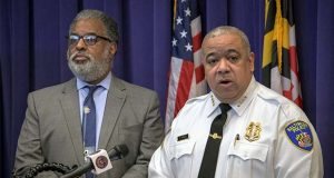FILE - In this Friday, Dec. 20, 2019 file photo, listens as Baltimore Police Commissioner Michael Harrison announces support for a pilot program that uses surveillance planes over the city to combat crime in Baltimore. City solicitor Andre Davis is at left. Baltimore could wrap up 2019 with its highest per-capita homicide rate on record as killings of adults and minors alike for drugs, retribution, money or no clear reason continue to add up and city officials appear unable to stop the violence.  (Jerry Jackson/The Baltimore Sun via AP)