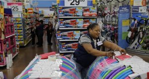 FILE - In this Nov. 27, 2019, file photo Balo Balogun labels items in preparation for a holiday sale at a Walmart Supercenter in Las Vegas. On Friday, Dec. 6, the U.S. government issues the November jobs report. (AP Photo/John Locher, File)
