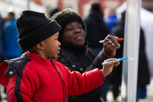 A west Baltimore child signs the Growing Together community board, one of the family events at the celebration dedication at Bon Secours Hospital. (Photo courtesy of LifeBridge Health)