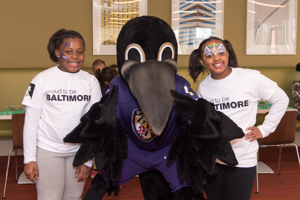Amani Thomas, left, and Ayanna Thomas spend time with Poe, the Baltimore Ravens mascot, at the Gameday Conversation event and Ravens watch party. (Photo courtesy of T. Rowe Price)