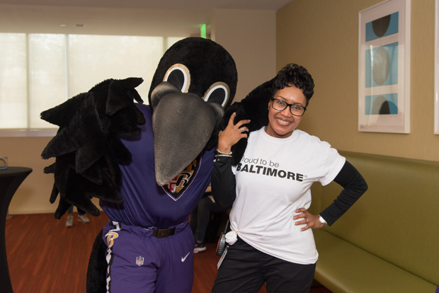 Renee Christoff, head of global associate engagement and corporate responsibility with T. Rowe Price, gets a photo with Baltimore Ravens mascot Poe during the watch party. (Photo courtesy of T. Rowe Price)