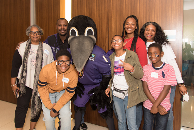 Baltimore Ravens mascot Poe gets a photo with, from left, Michelle Carter, Britney Carter, Cari Carter, Carter March, Raegan McCallister, Jason Whittington Sr. and Jason Whittington, Jr. (Photo courtesy of T. Rowe Price)