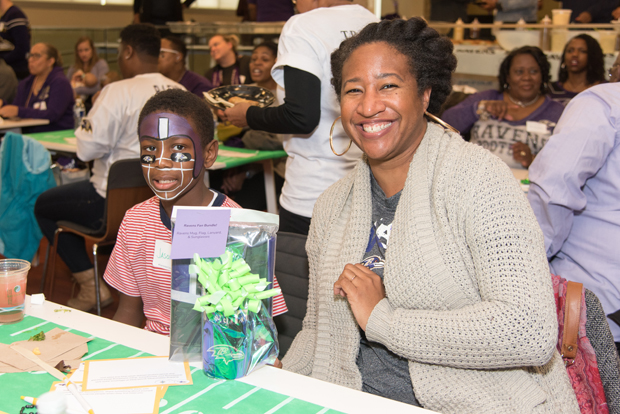Kaleema Obot, a community liaison for the 9th District, enjoys the event with her son, Jason. (Photo courtesy of T. Rowe Price)
