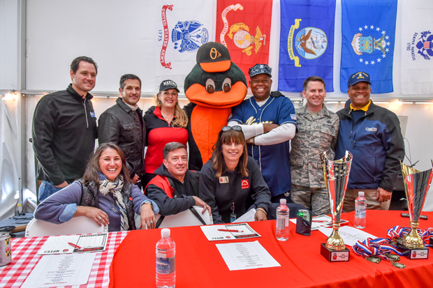 From left, Stars, Stripes & Chow judges Jonathan Myers, a meteorologist with WBFF-TV; Lou Kousouris, executive vice president at Artemis properties and honorary event chair; Dianne Bradley, office manager at SubCom; Paul Martin, assistant clinical director at The Baltimore Station; Matthew Hackner; and Vince Patton, senior vice president for leadership development at NewDay USA, pose for a photo with the Orioles Bird and Christie Walsh-Myers, event chair and president of The Baltimore Station's Board of Directors; John Friedel, executive director of The Baltimore Station and Kim Callari, director of development and communications at The Baltimore Station. (Photo courtesy of The Baltimore Station)