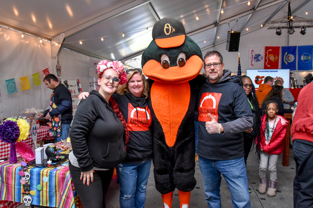 Shelby Smith, left, assistant kitchen manager at The Baltimore Station, and Mindy and Jay Hinsley from the Society of American Military Engineers (SAME), get a photo with The Oriole Bird during the Stars, Stripes & Chow event. SAME sponsored The Baltimore Station's team and assisted with the booth at the event. (Photo courtesy of The Baltimore Station)