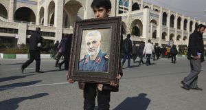 "A boy carries a portrait of Iranian Revolutionary Guard Gen. Qassem Soleimani, who was killed in the U.S. airstrike in Iraq, prior to the Friday prayers in Tehran, Iran, Friday Jan. 3, 2020. Iran has vowed ""harsh retaliation"" for the U.S. airstrike near Baghdad's airport that killed Tehran's top general and the architect of its interventions across the Middle East, as tensions soared in the wake of the targeted killing. (AP Photo/Vahid Salemi)"