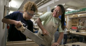 In this Aug. 18, 2014 photo, student Samantha Santana, left, gets instruction from Kathleen Klohe during a training session conducted by Nontraditional Employment for Women, to train women for employment in the construction trades, in New York. About 7.1 million Americans were employed in construction-related occupations in 2013, and only 2.6 percent were women. In firefighting, women comprise a higher share of the workforce at 3.5 percent. (AP Photo/Richard Drew)