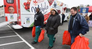 Photo: Perdue associate Dan Hudson, right, helps local residents with bags of food they received from the Maryland Food Bank's new Mobile Market on Thursday, Feb. 20 at the food bank's branch in Salisbury, Md.