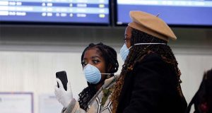 Women wear face masks at the Roissy Charles de Gaulle airport, north of Paris, Thursday, March 12, 2020. The European Union on Thursday will evaluate President Donald Trump's decision to restrict travel from Europe to the United States amid deep concern over the economic impact of the move with markets already heavily hit by coronavirus. For most people, the new coronavirus causes only mild or moderate symptoms, such as fever and cough. For some, especially older adults and people with existing health problems, it can cause more severe illness, including pneumonia. (AP Photo/Thibault Camus)