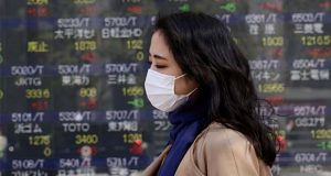 A woman walks by an electronic stock board of a securities firm in Tokyo, Wednesday, March 18, 2020. Major Asian stock markets are higher after Wall Street rallied on President Donald Trump's promise to prop up the economy through the coronavirus outbreak. (AP Photo/Koji Sasahara)