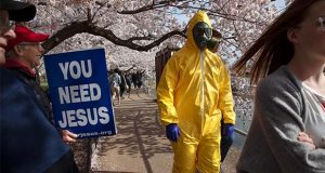 "A 17-year-old who asked not to be named, wears a hazmat suit, gas mask, boots, and gloves as he walks past people holding a sign that says, ""you need Jesus"" as he and his family from Gaithersburg, Md. walk under cherry blossom trees in full bloom along the tidal basin, Sunday, March 22, 2020, in Washington. ""I'm not worried for me since I'm young,"" says the 17-year-old, ""I'm wearing this in case I come into contact with anyone who is older so that I won't be a threat to them."" He plans to wear his protective outfit for coronavirus each time he leaves the house. Sections of the National Mall and tidal basin areas have been closed to vehicular traffic to encourage people to practice social distancing and not visit Washington's iconic cherry blossoms this year due to coronavirus concerns. The trees are in full bloom this week and would traditionally draw a large crowd. (AP Photo/Jacquelyn Martin)"