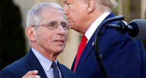 Dr. Anthony Fauci, director of the National Institute of Allergy and Infectious Diseases, takes the podium to speaks about the coronavirus in the Rose Garden of the White House, Monday, March 30, 2020, in Washington, as President Donald Trump listens. (AP Photo/Alex Brandon)