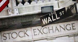 FILE - This July 16, 2013 file photo shows a street sign for Wall Street outside the New York Stock Exchange in New York.  Stocks are opening slightly lower on Wall Street, Tuesday, March 31, 2020, as investors close out a brutal month of March. The S&P 500 is headed for its biggest quarterly decline since the last quarter of 2008.(AP Photo/Mark Lennihan, File)
