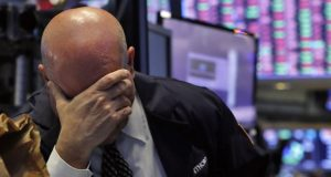 A trader has his head in his hand on the floor of the New York Stock Exchange, Thursday, March 12, 2020. The stock market had its biggest drop since the Black Monday crash of 1987 as fears of economic fallout from the coronavirus crisis deepened. The Dow industrials plunged more than 2,300 points, or 10%. The vast majority of people recover from the new coronavirus. According to the World  Health Organization, most people recover in about two to six weeks, depending on the severity of the illness. (AP Photo/Richard Drew)