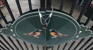 Locked gates and empty walkways are shown at Oriole Park at Camden Yards, home of the Baltimore Orioles baseball team. Unions are pushing for Major League Baseball to pay stadium workers hurt by the delay of the regular season, initially slated to begin this month. (AP Photo/Steve Helber)