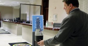 Del. Wayne Hartman, a Republican state legislator in Maryland who represents parts of Wicomico and Worcester counties, stops at a hand-sanitizer dispenser on the ground floor of the Maryland State House on Friday, March, 6, 2020, in Annapolis, Md. The dispenser was placed near an entrance this week state officials are urging people to keep calm but take precautions due to coronavirus. (AP Photo/Brian Witte)