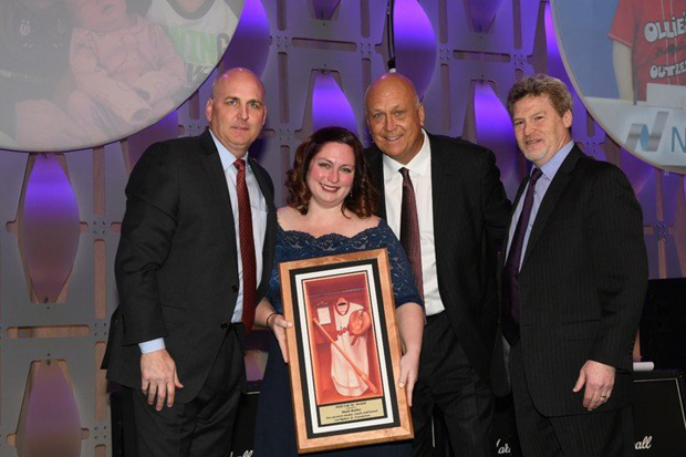 Brooke Butler, second from left, the daughter of the late Mark Butler, accepts an award on her father's behalf for raising $12 million over the course of 12 years for the Cal Ripken Sr. Foundation. Mark Butler was the founder and CEO of Ollie's Bargain Outlet and became the chairman of the foundation's board of directors in 2014. Joining Brooke Butler for the presentation are, from left, Bill Ripken, Baseball Hall of Famer Cal Ripken Jr. and Steve Salem, president and CEO of the Cal Ripken Sr. Foundation. (Photo by Robert Smith Photography)