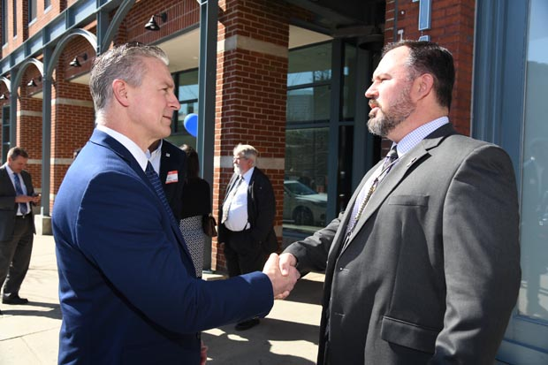 Volunteers of America Chesapeake and Carolinas President/CEO Russ Snyder, left, shakes hands with Chris Bruser, chief of social work service for the VA Health Care System. (Photo by Maximilian Franz)