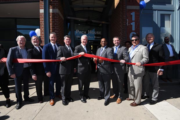 """From left, James Campbell, a principal with Somerset Development; Bill Whitman, development partner with Somerset Development; Russ Snyder, president/CEO of Volunteers of America Chesapeake and Carolinas, Kenneth Holt, Secretary of Maryland Department of Housing and Community Development; U.S. Sen. Chris Van Hollen, D-Md.; Baltimore Mayor Bernard C. """"Jack"""" Young; Baltimore City Councilman Eric Costello; Gary Garofalo, president and CEO of Harkins Builders; and Patrick Sheridan, the vice president of housing for the national chapter of Volunteers of America, participate in a ribbon-cutting ceremony officially opening Paca House, which underwent a $26.8 million renovation. (Photo by Maximilian Franz)"""